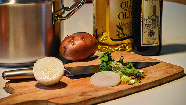 onion on chopping board beside olive oil